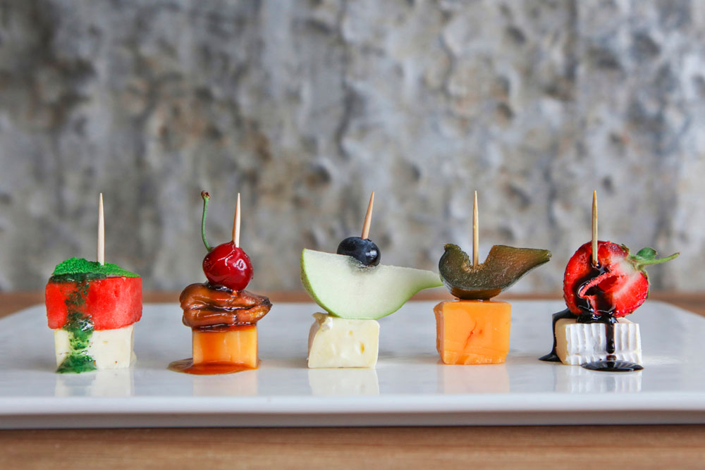 Fruit and cheese kebabs on a plate showcasing fruit and cheese pairings.